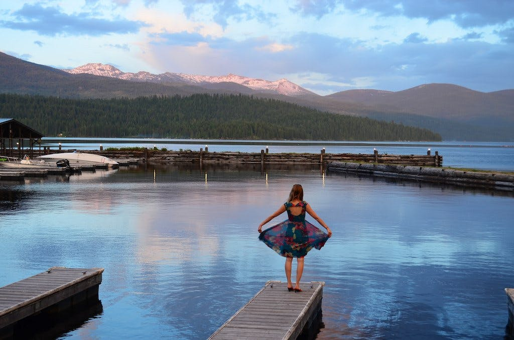 woman standing on the edge of dock, with mountains in the background