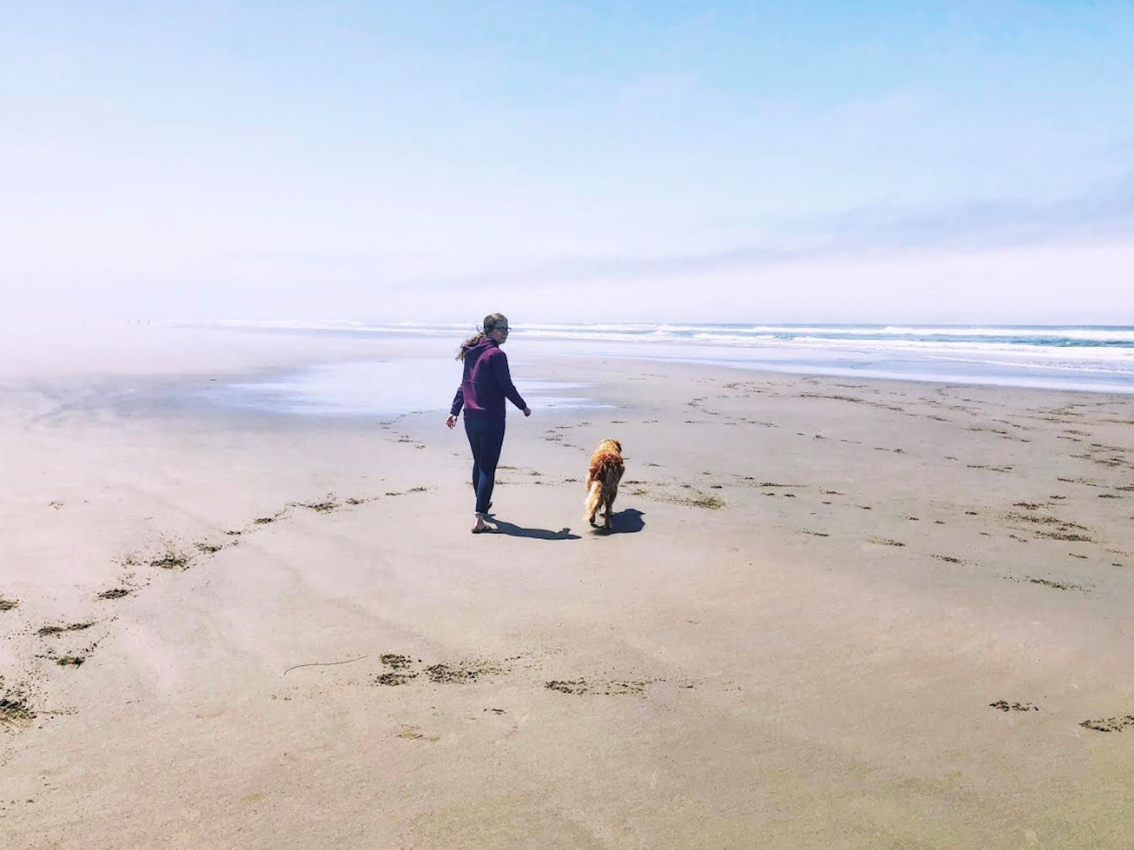 Rusty and his owner walking along the beach in Pacific City, OR