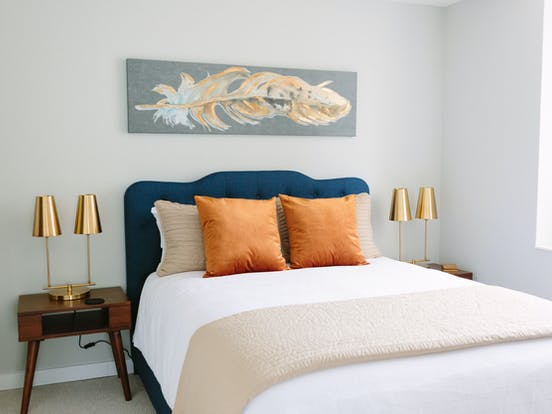 Inside a bright bedroom with a professionally well-made bed with modern style night stands.