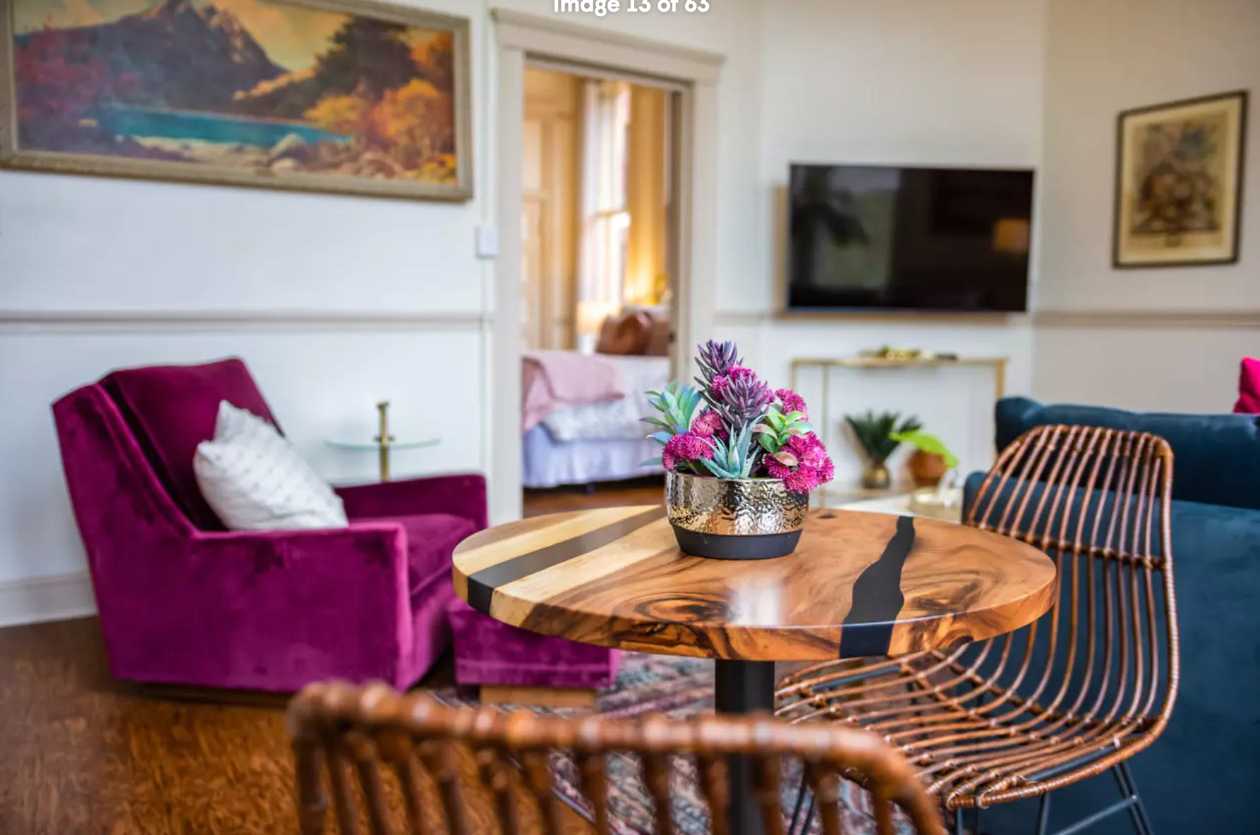 interior of vacation rental with velvet arm chair and wood bistro table topped with a succulent plant