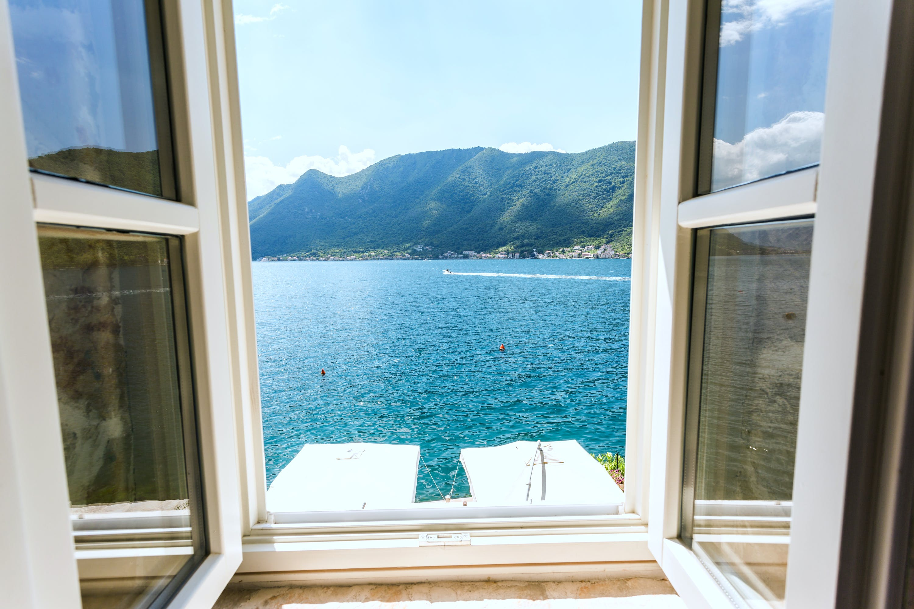 view through an open window of a beautiful lake