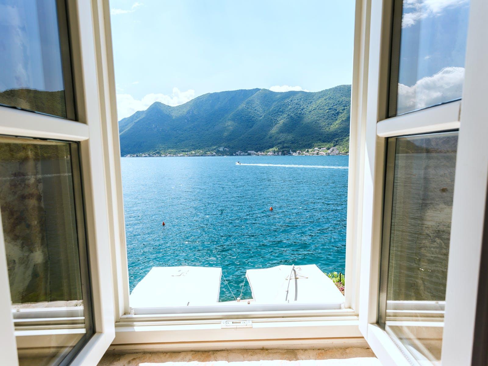 view through an open window of a beautiful lake