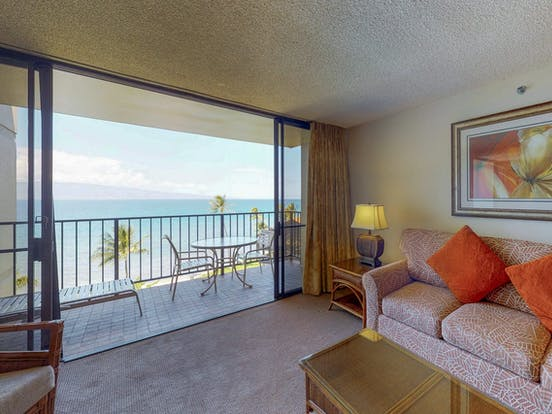 Vacation rental with open doors leading to balcony with ocean views