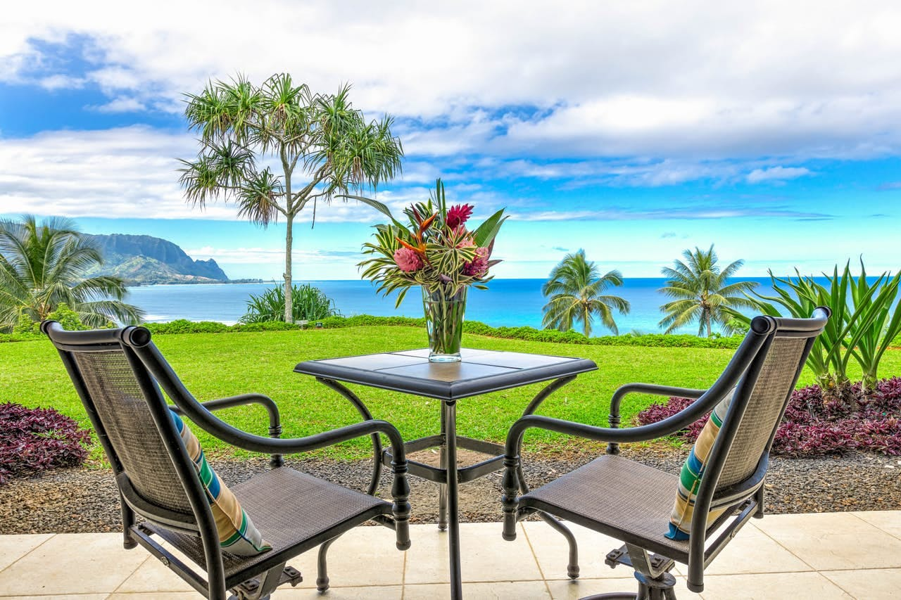 two chairs sitting on a patio overlooking the pacific ocean on kauai