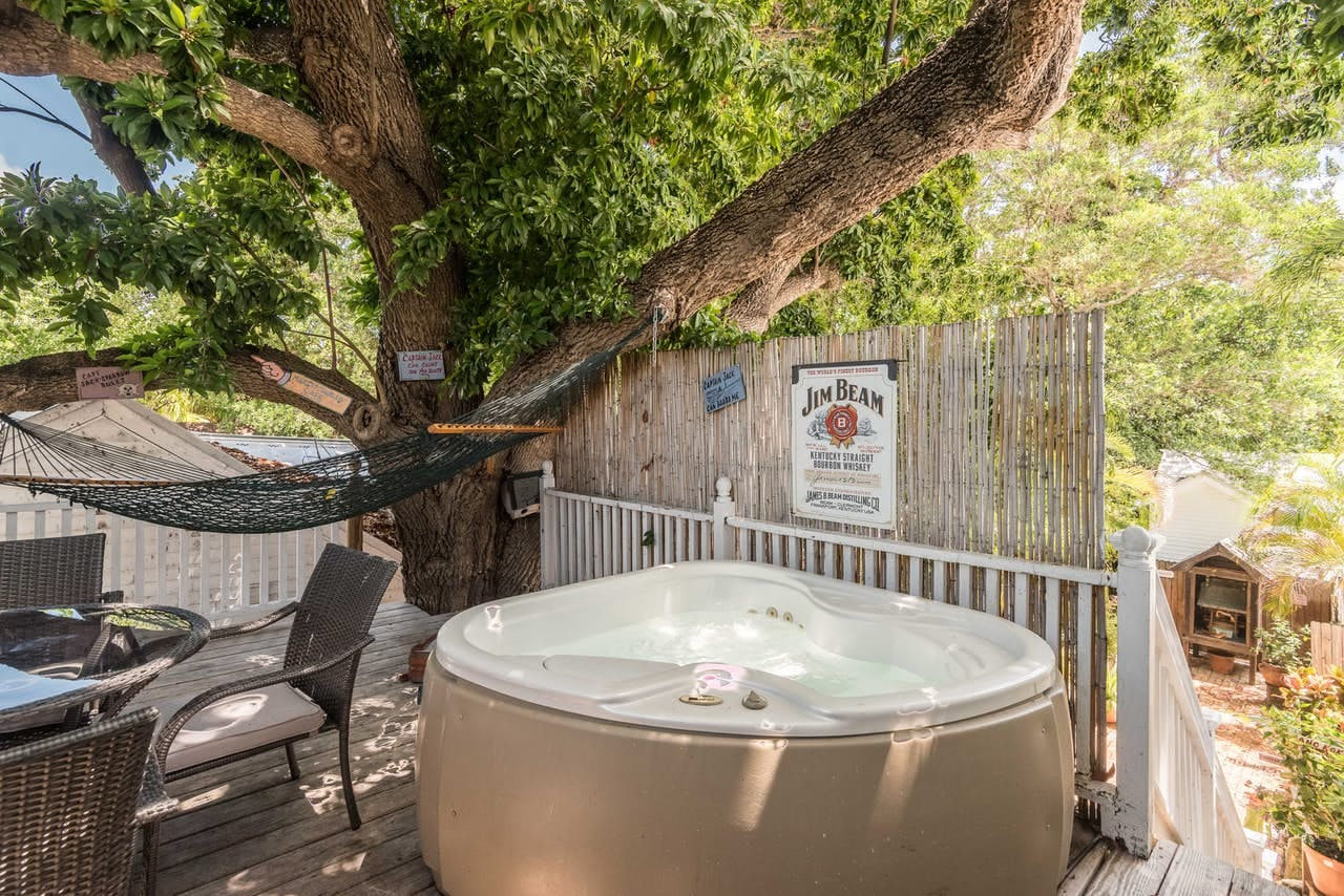 a hot tub and hammock in the backyard of a key west home