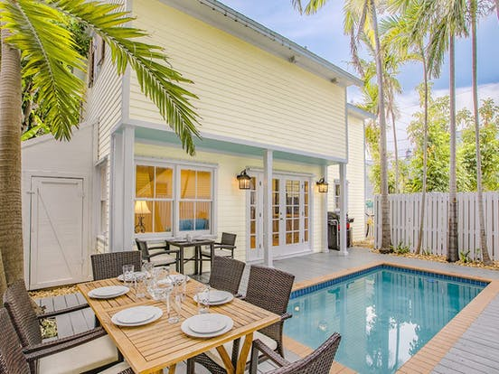 Backyard of Key West cottage with dining furniture and pool
