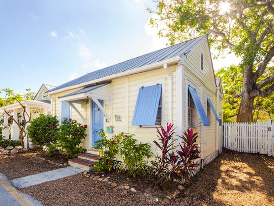 Light blue shutters and yellow siding of Key West cottage rental