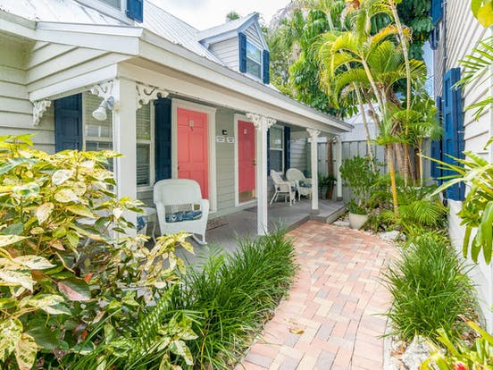 Blue shutters and coral colored doors of Key West vacation cottage