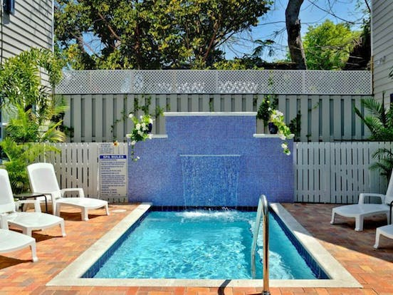 Outdoor pool with waterfall feature and lounge chairs in Key West, FL
