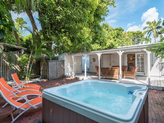 Backyard of Key West cottage with lounge chairs and private hot tub