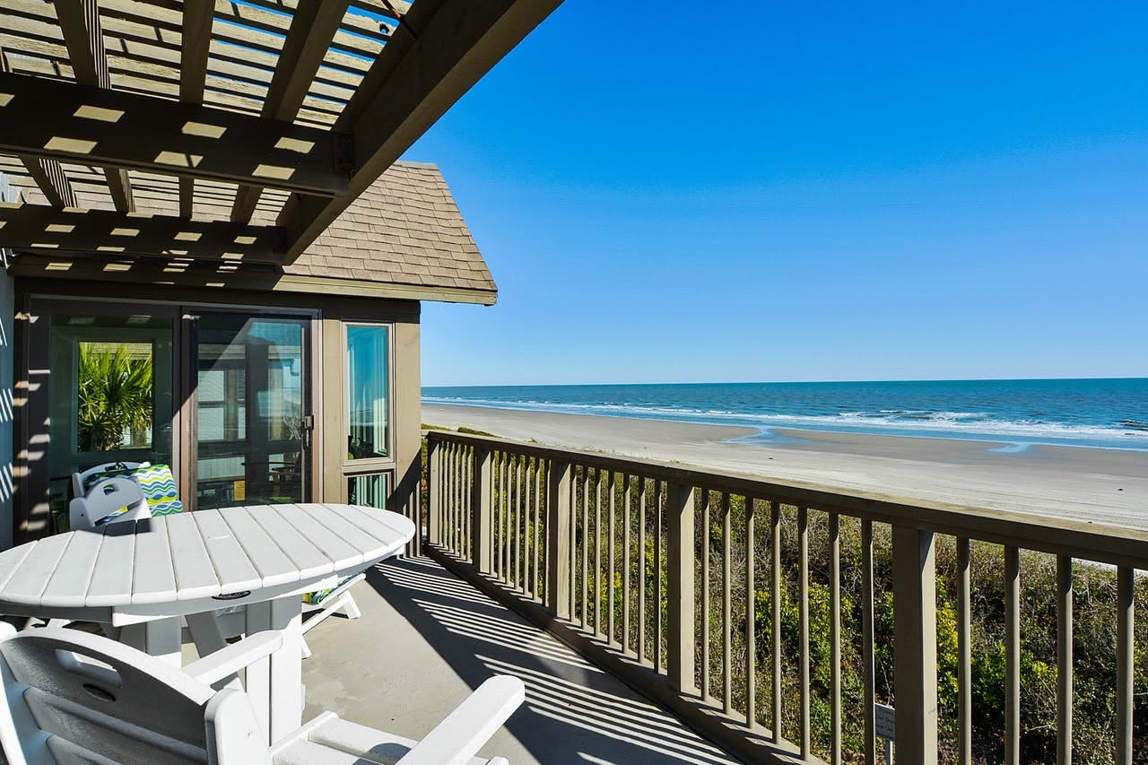 a deck with a table and chair overlooking the ocean on a sunny day on kiawah island