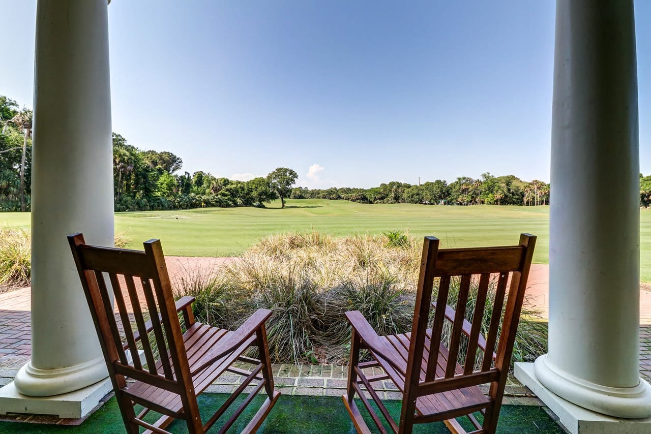 two rocking chairs overlooking a golf course on a cloudless day