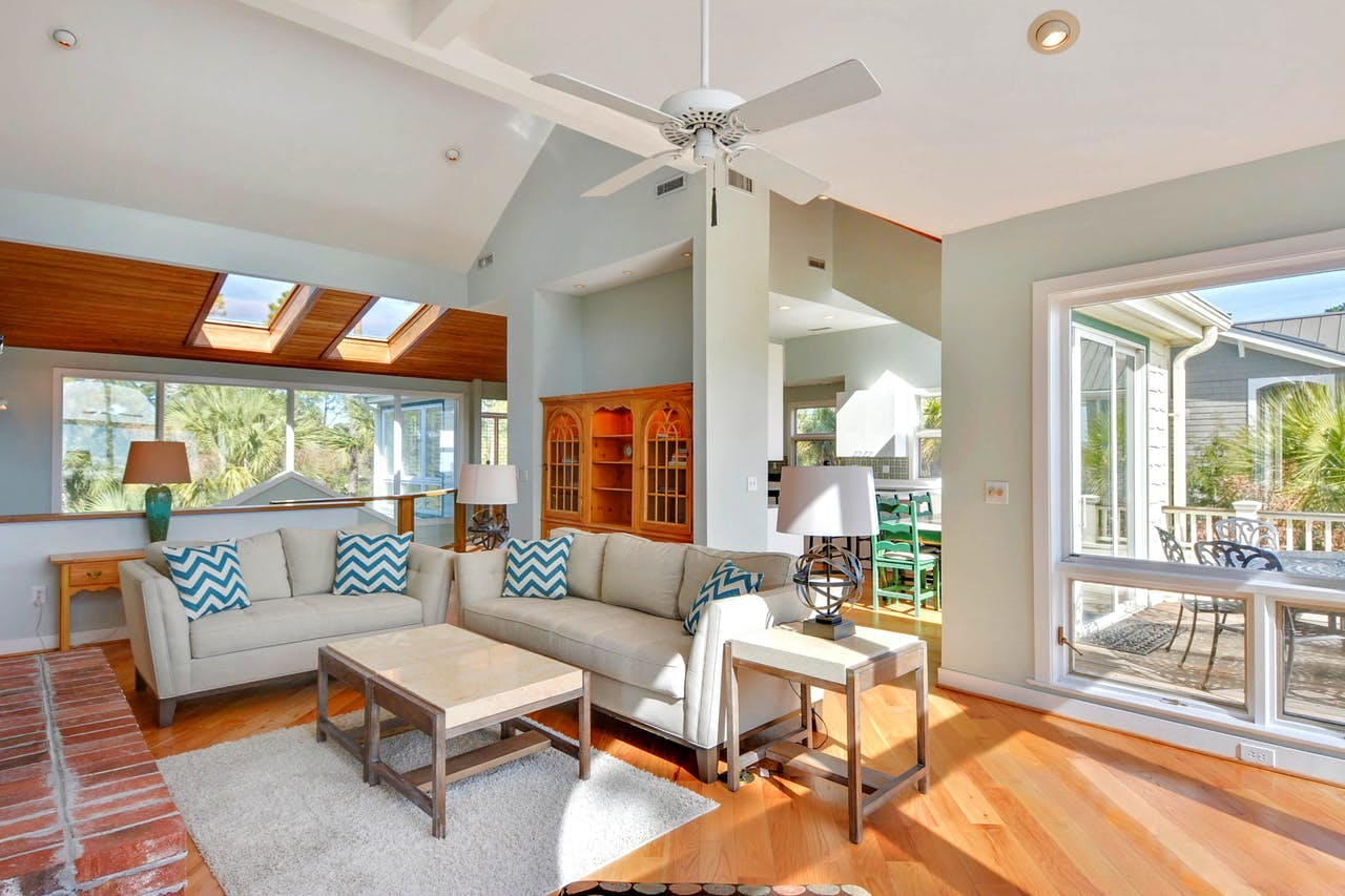 a bright living room with lots of windows and incoming sunlight