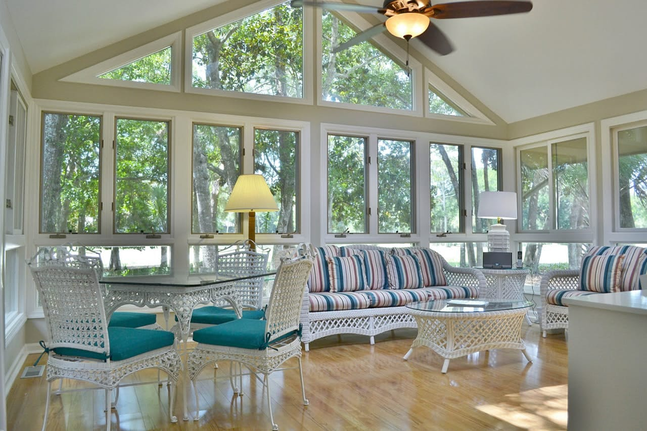 a sun room with white furniture in a vacation home on kiawah island