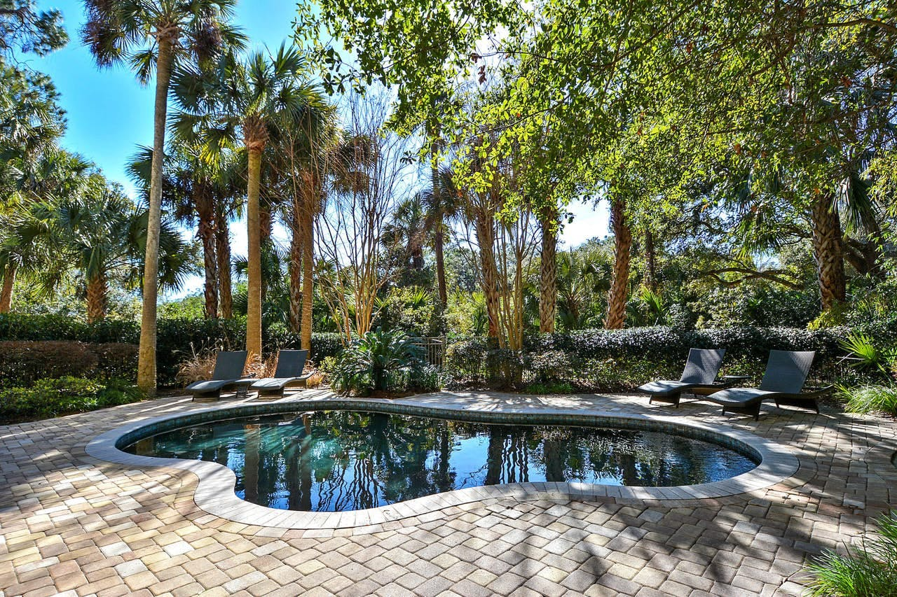 a private pool surrounded by palm trees in a home's backyard