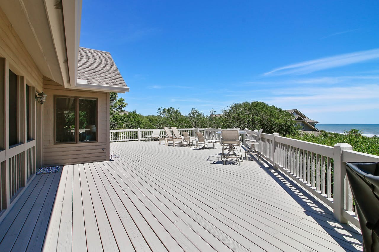 a large deck with several sun chairs with a view of the ocean