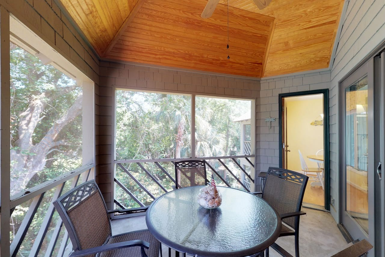 an outdoor table with three chairs on the deck of a kiawah island condo