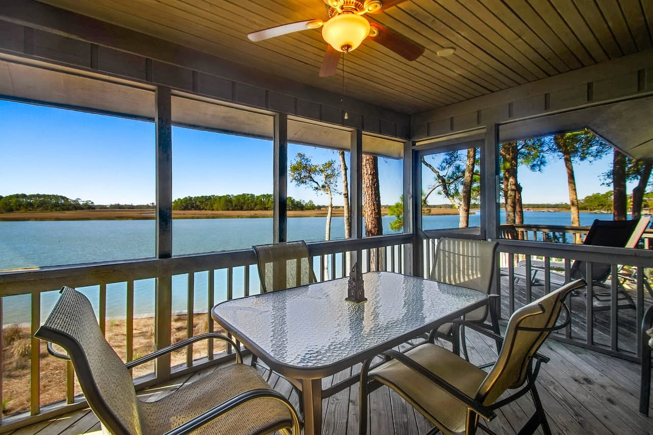 a back porch with a chairs and a table overlooking water on kiawah island