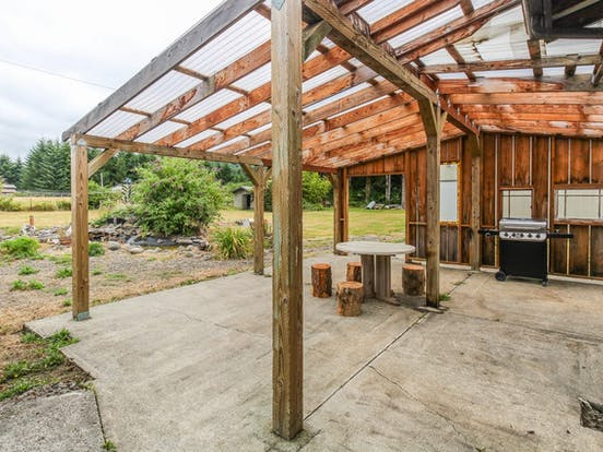 Covered outdoor area with table, chairs, and a grill at La Push, WA vacation rental