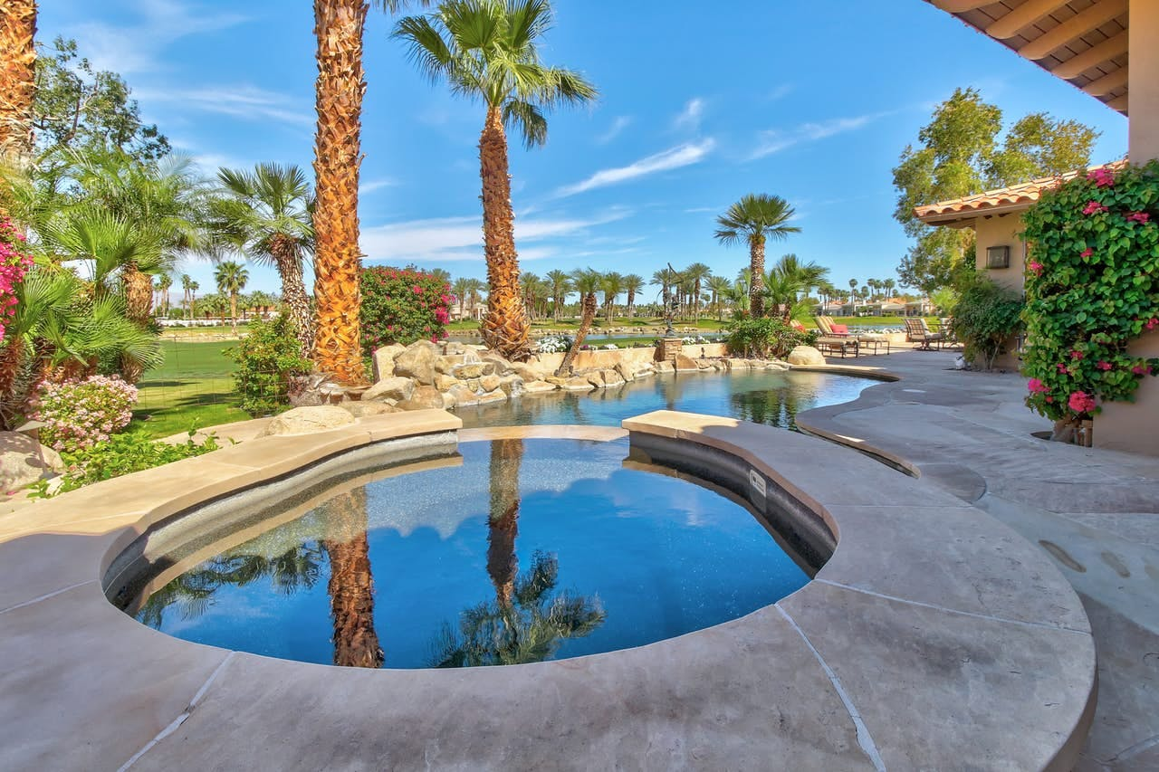 a vacation home in La Quinta with a private pool and a golf course alongside it