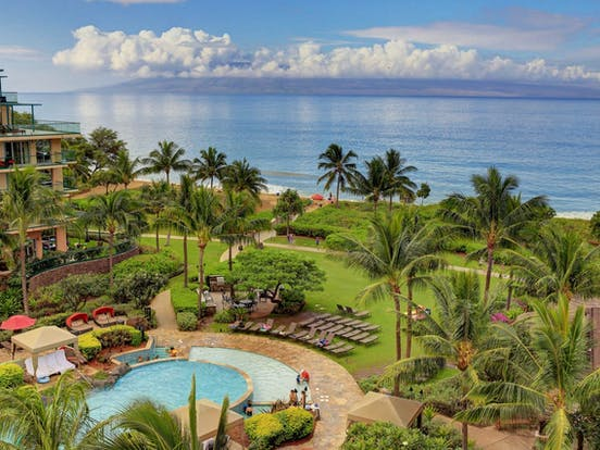 Outdoor pool, ample lounge chairs, green grass and ocean views from Honua Kai Resort