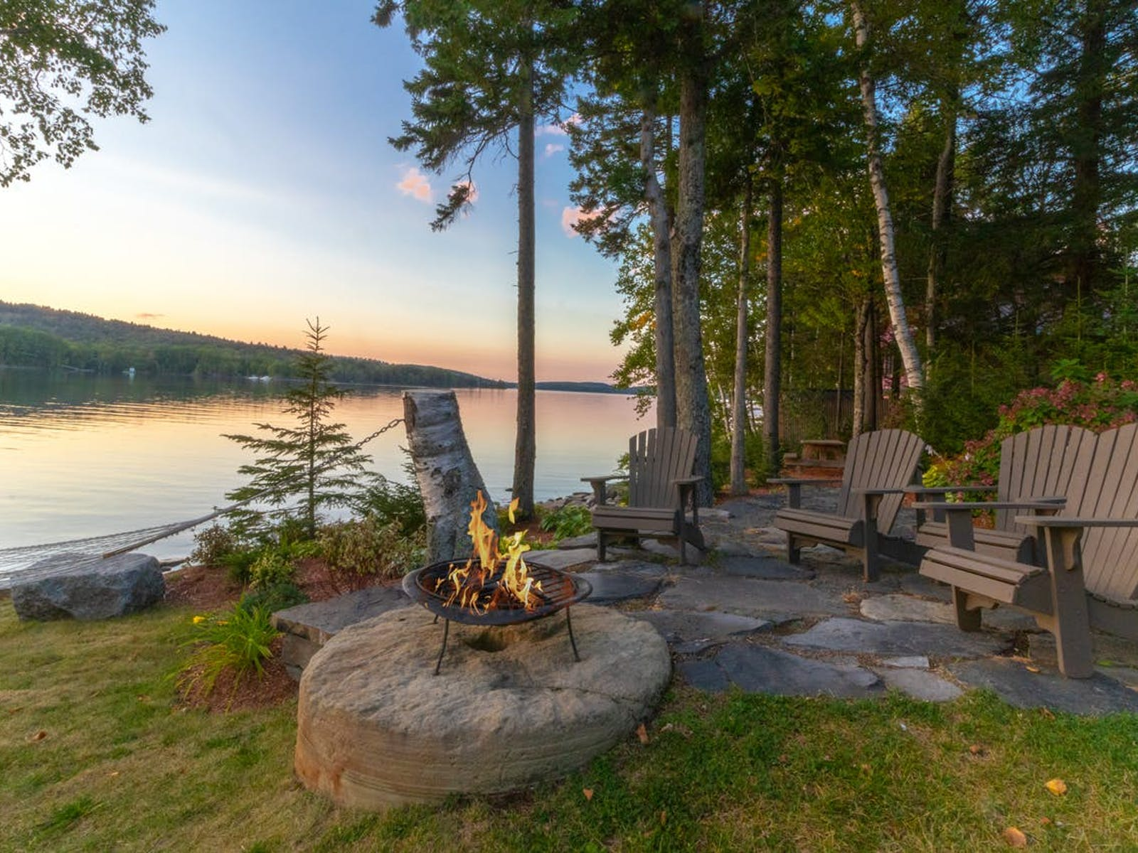Lakefront vacation rental fire-pit with hammock and seating