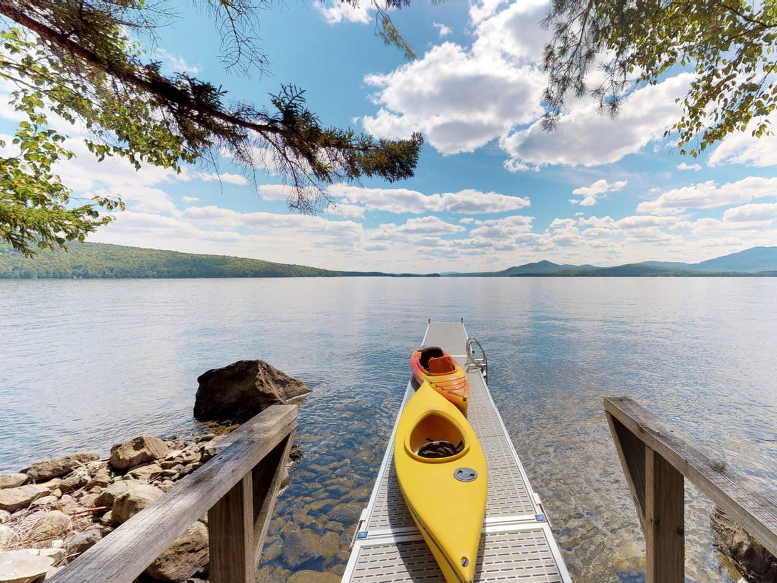 Vacation rental dock with kayaks extending over lake