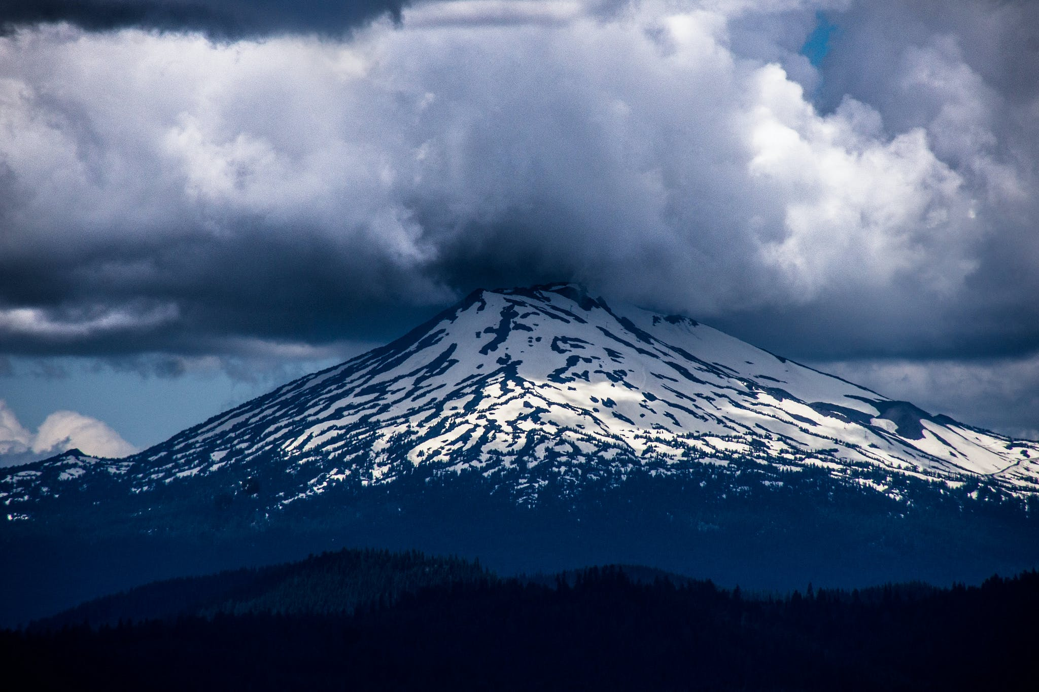 a view of mt bachelor with a cloud hovering over the peak