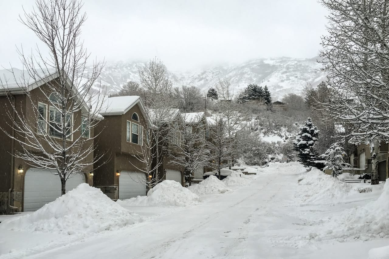 a snowy neighborhood in Alta with a row of houses on each side