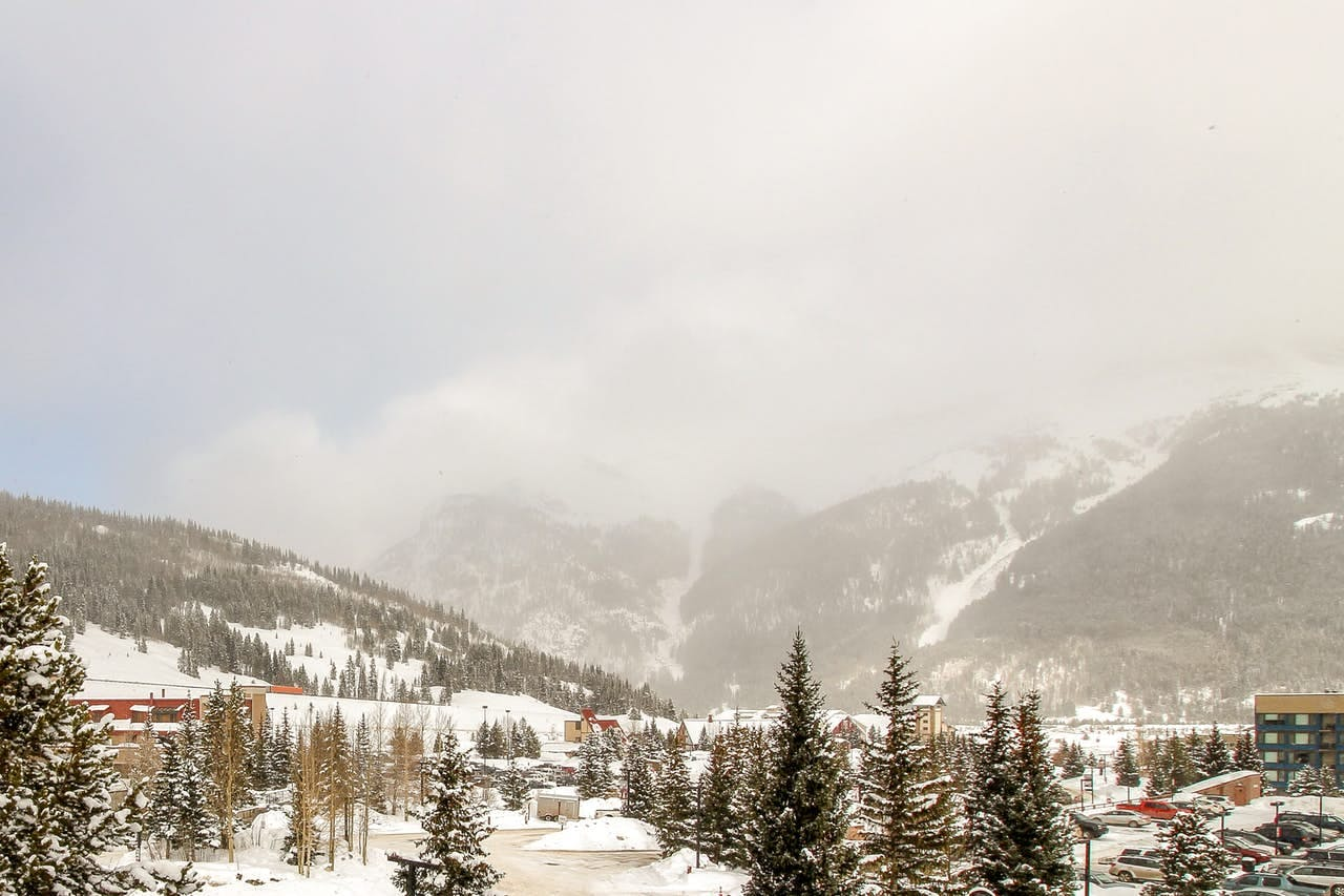 a landscape photo of snow falling over Copper Mountain