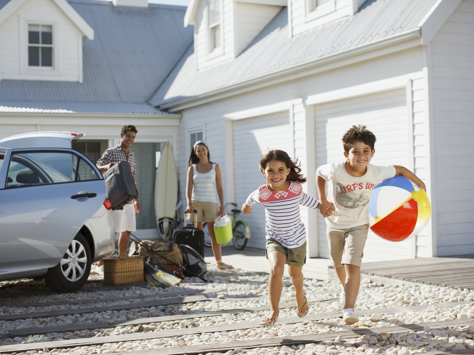 Family loading up car for the beach in vacation rental driveway