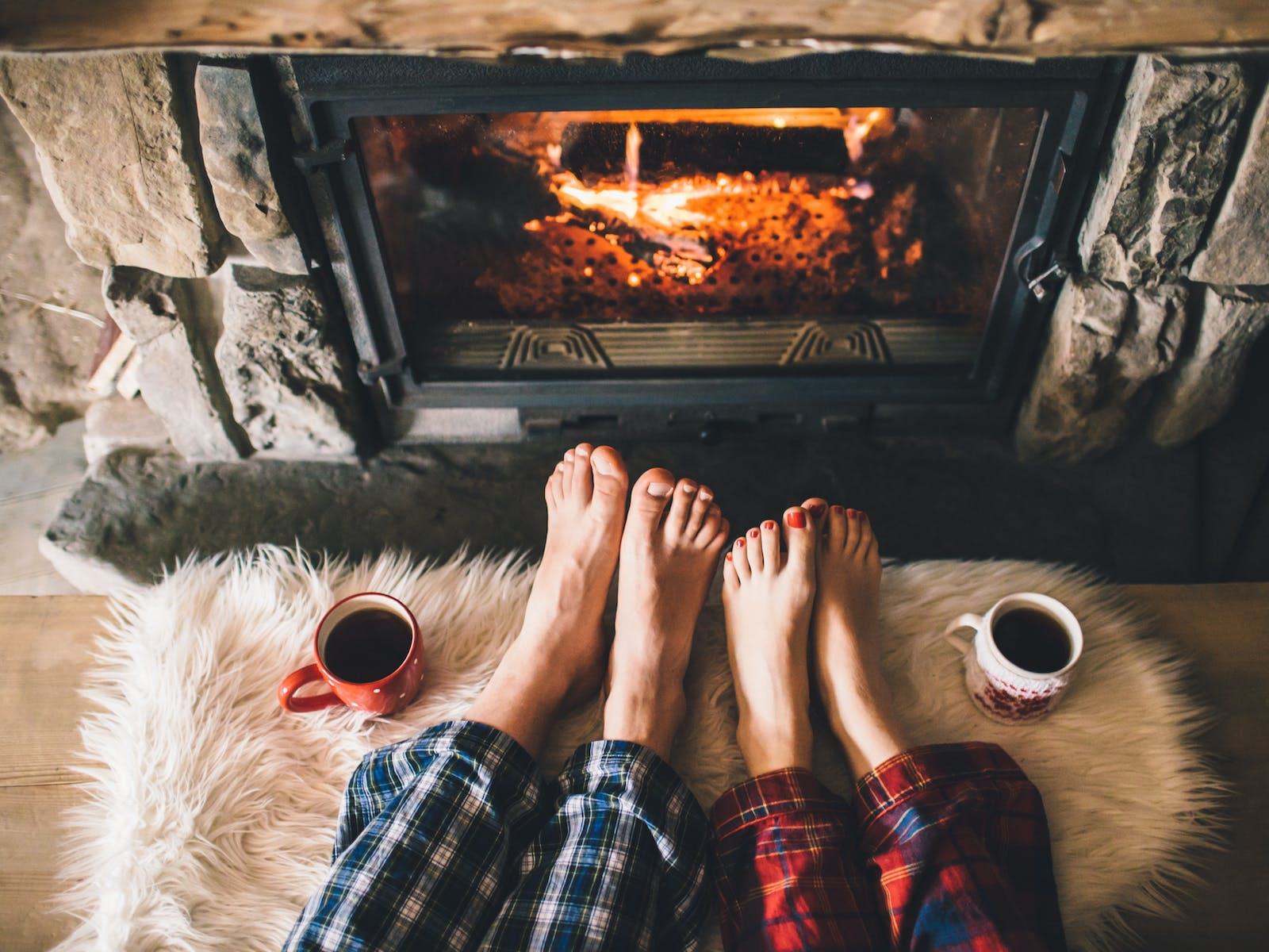 Two people in pajamas warming their feet by the fire