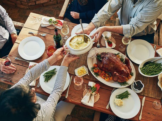 Friends sharing a holiday meal over a wooden dining table