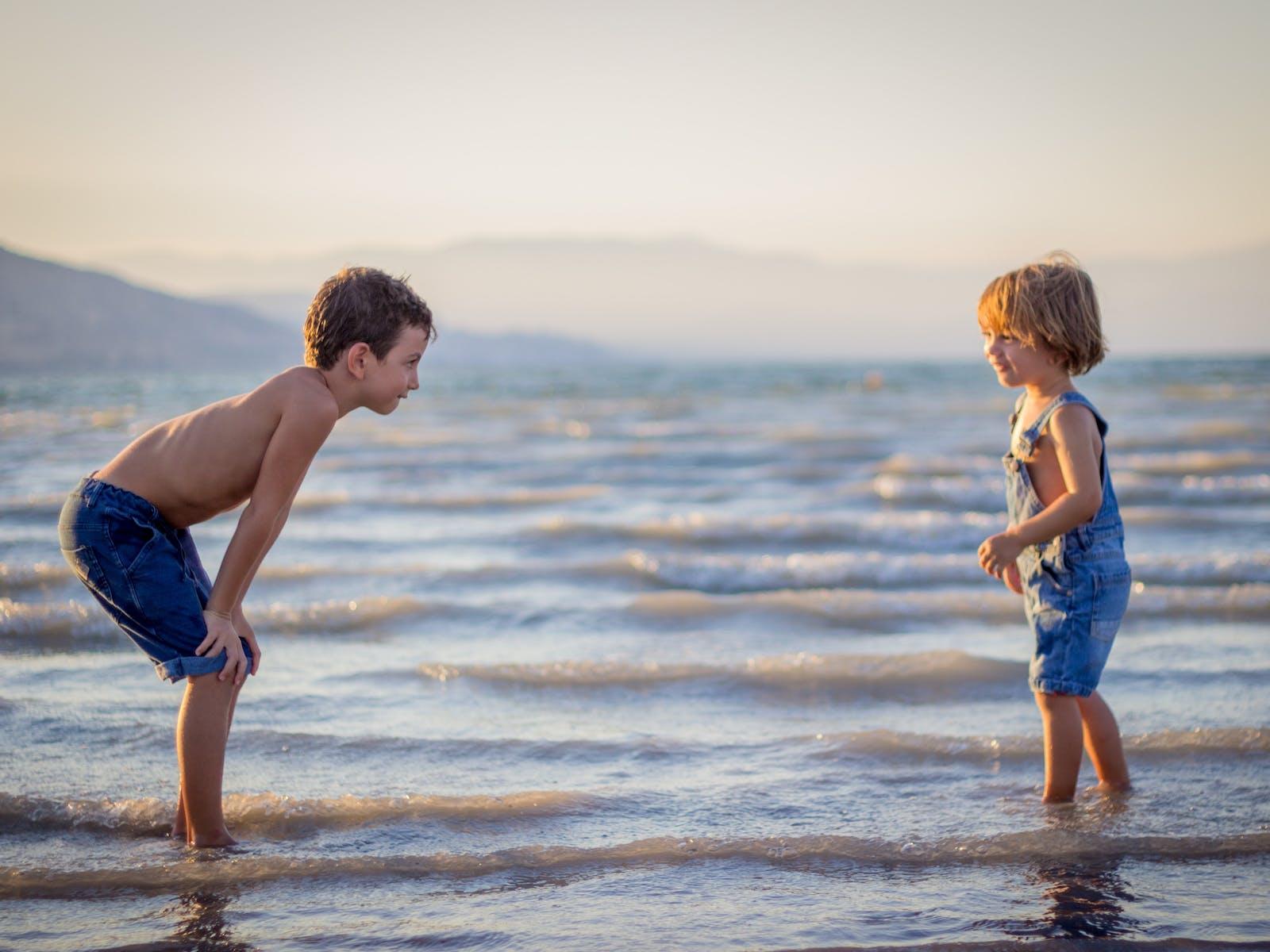 siblings play on the beach
