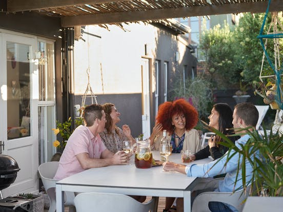 Group enjoying wine around a vacation rental outdoor patio table