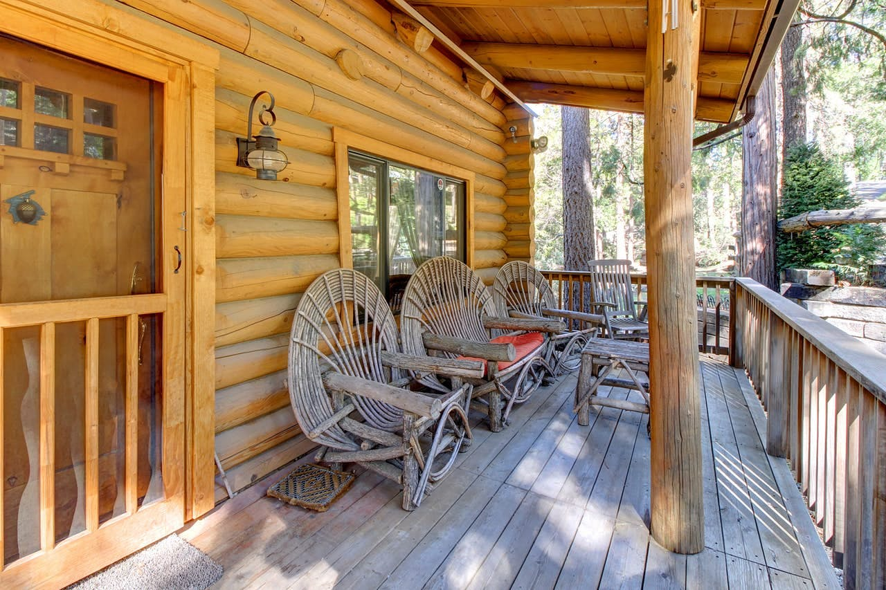 custom wicker chairs on the porch of a log cabin