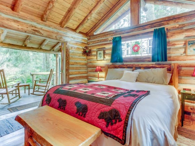 a bedroom in a cabin with doors that open up to a porch overlooking a pond