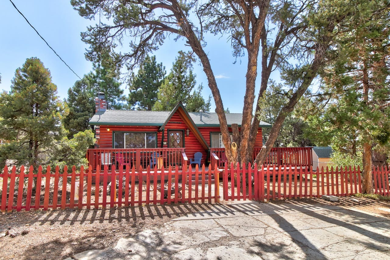 a red log cabin with a red picket fence in big bear city, ca