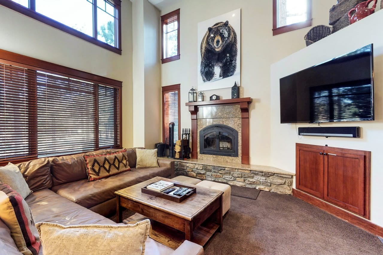 Rustic living area with large artwork of a bear, fireplace and TV