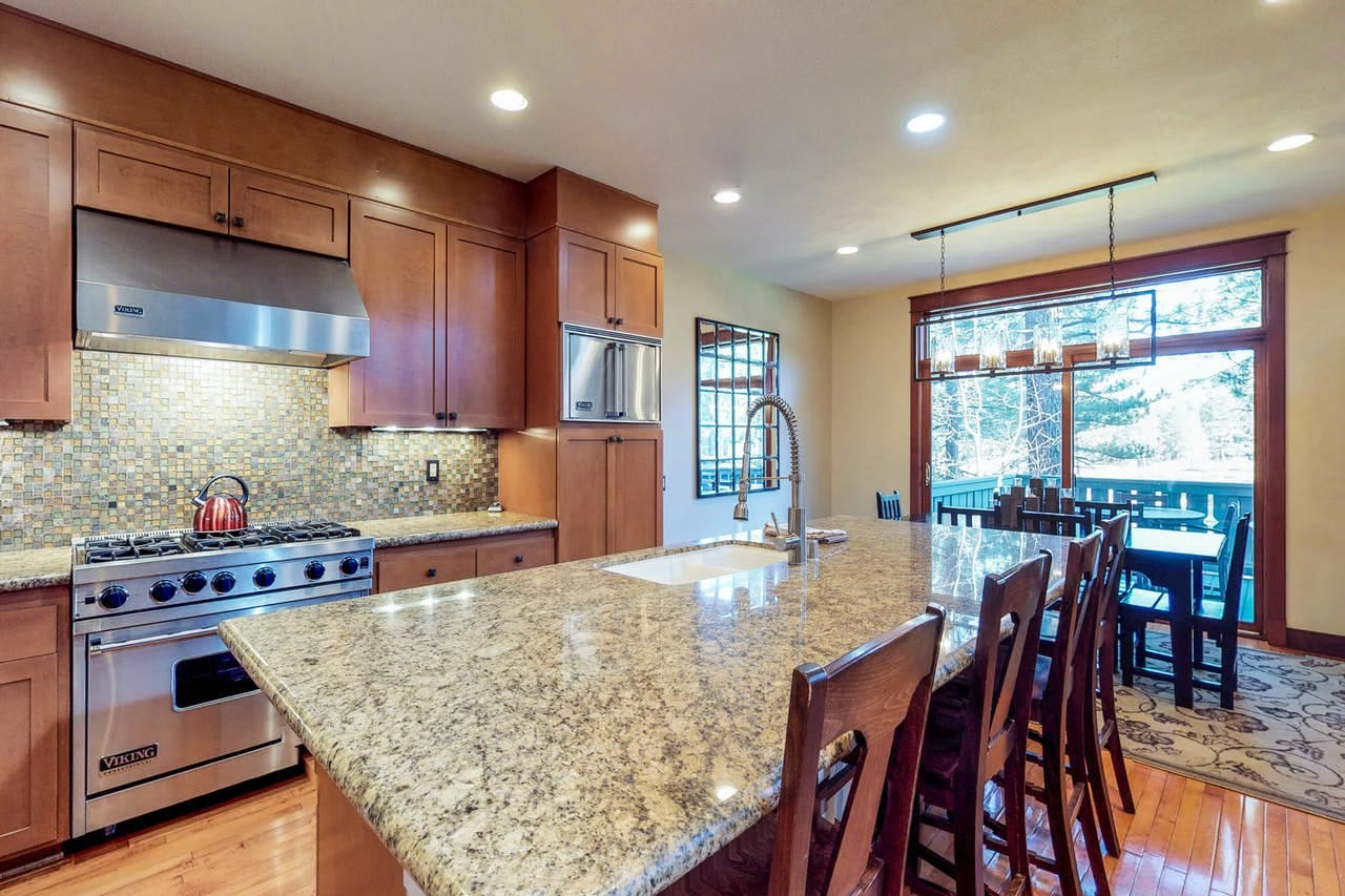 Kitchen with marble countertops, stainless steel appliances and adjacent dining area