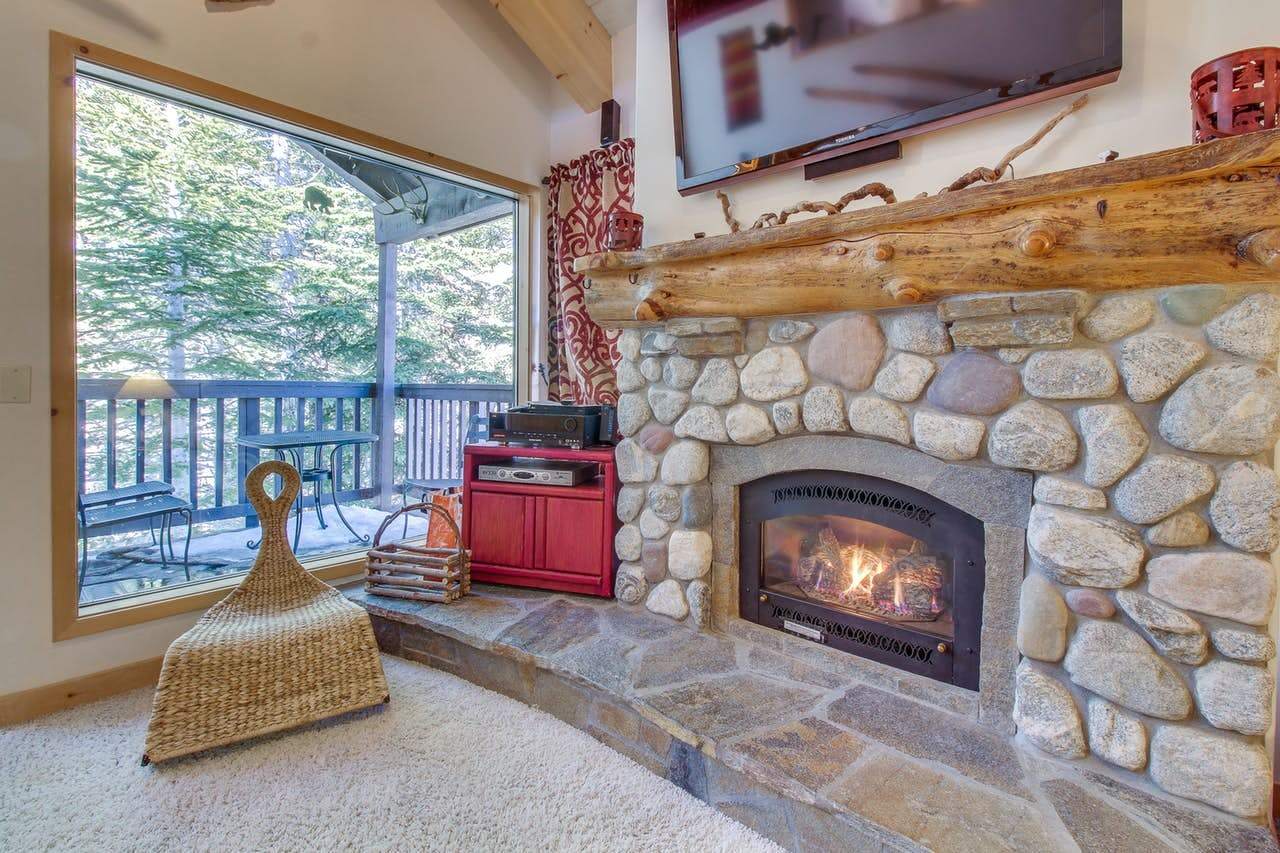 Stone fireplace and view of outdoor patio of vacation rental in Mammoth Lakes, CA
