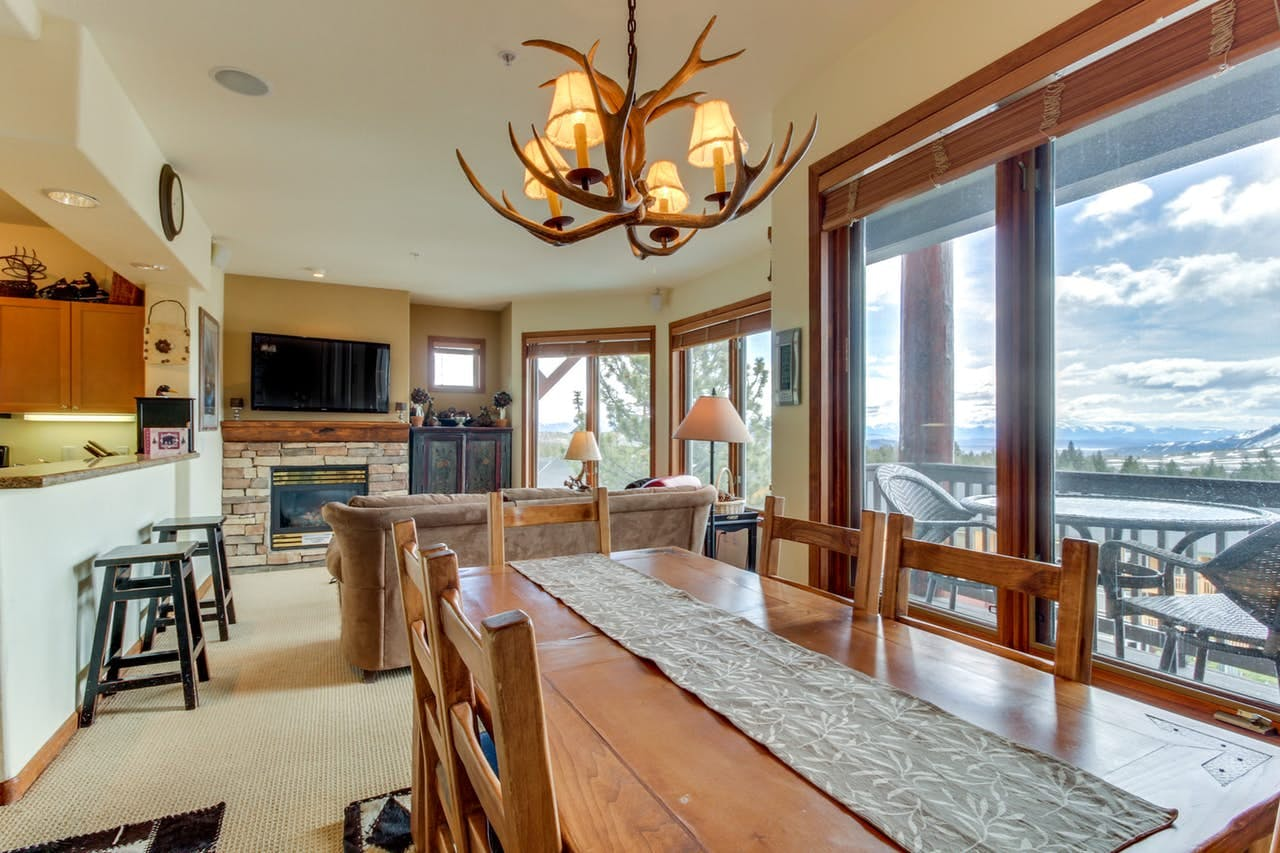 Vacation rental in Mammoth Lakes featuring a gas fireplace, breakfast bar, kitchen, dining room table and deck with mountain views