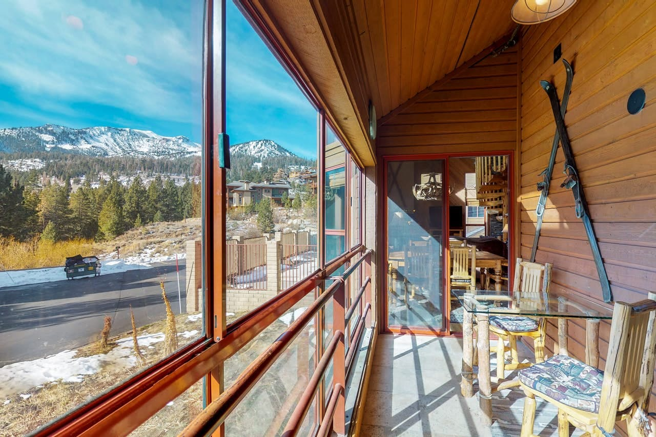 A sun-room with a small dining area and comfortable seating for views of the surrounding mountains and the sun in Mammoth Lakes, CA