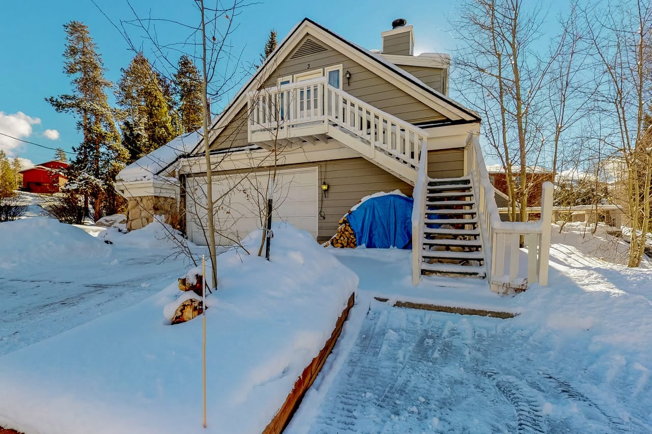 Vacation home exterior and driveway covered in snow