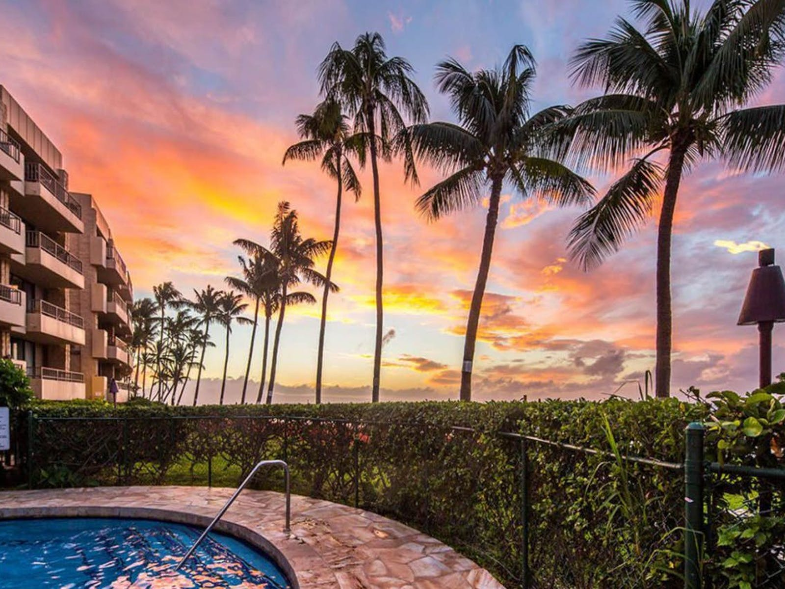 a sunset in maui that can be seen from a hot tub near the beach
