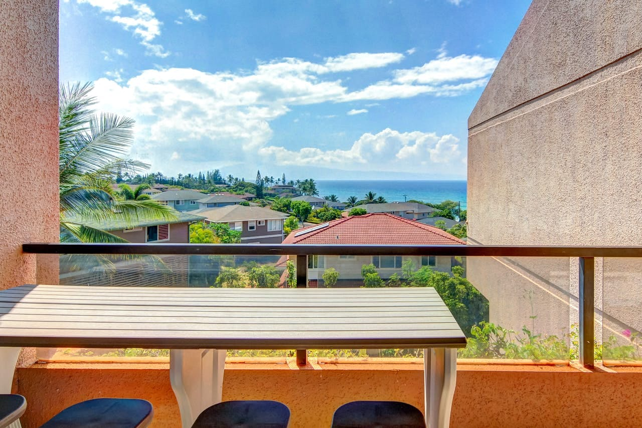 a table on a deck that overlooks Maui with the ocean in the distance