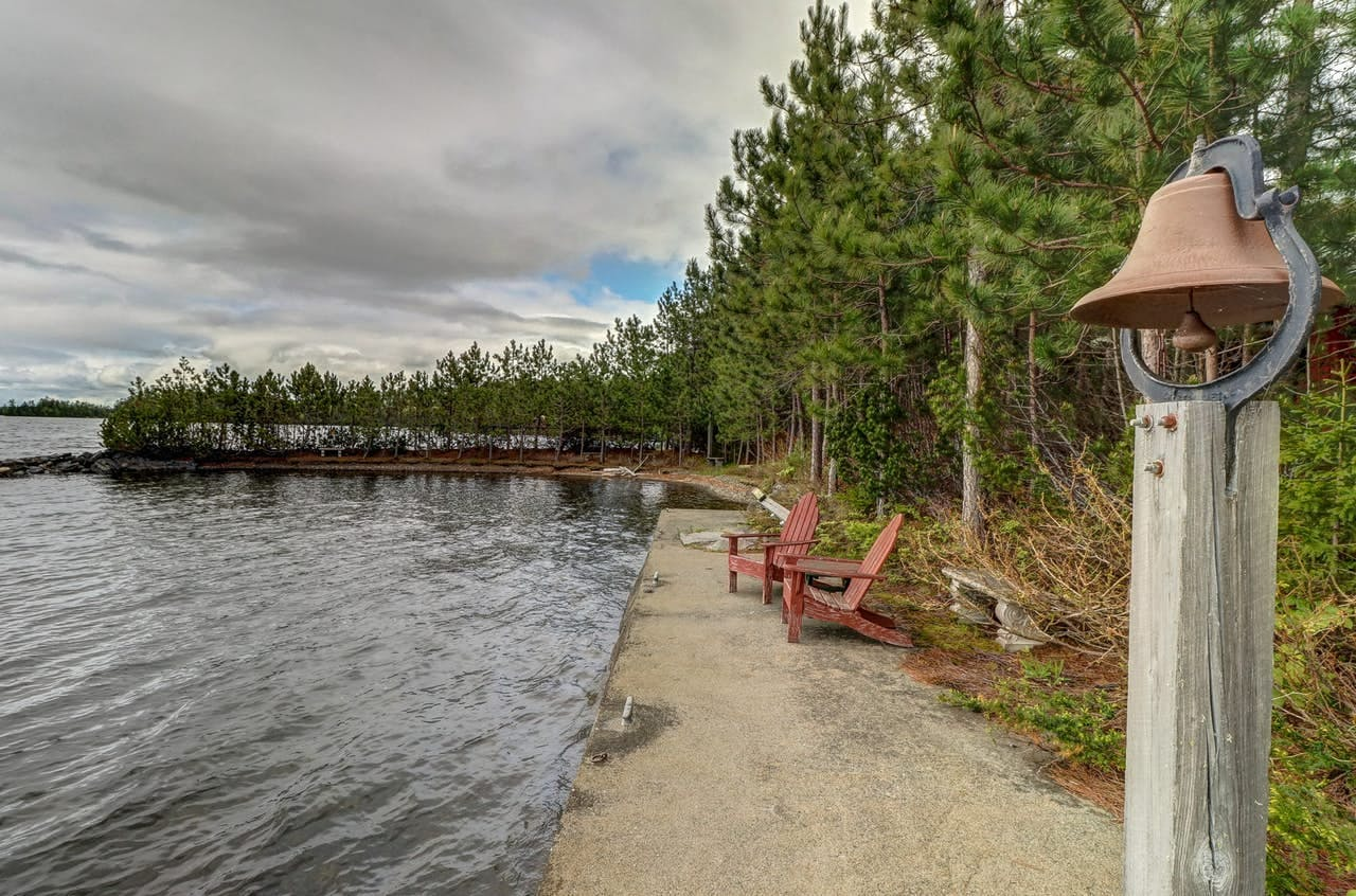 two Adirondack chairs sitting on the shore overlooking moosehead lake