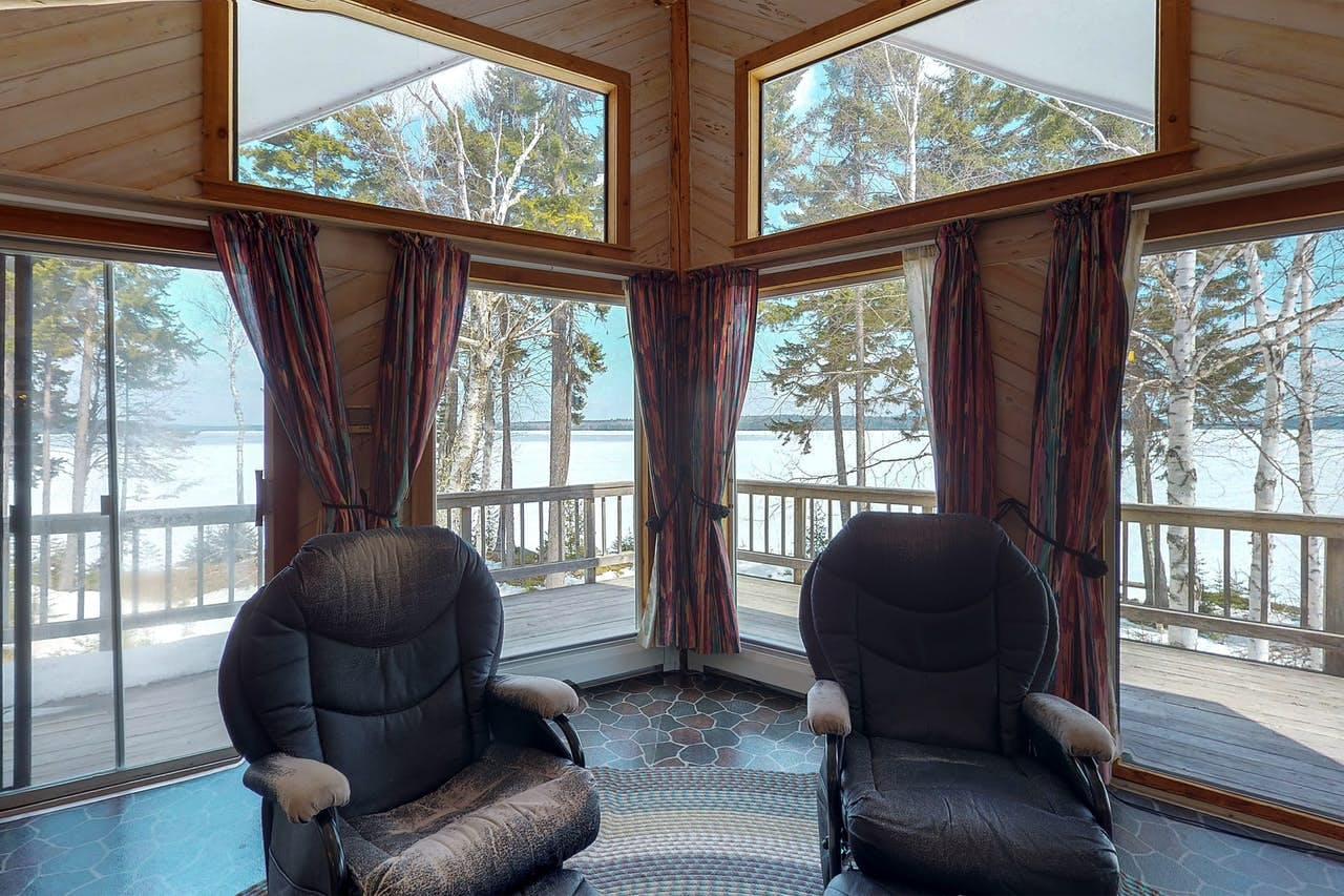 two recliner chairs in a living rooms, with windows behind them overlooking moosehead lake