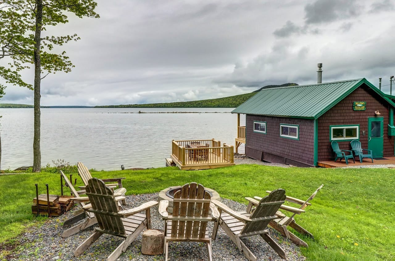 chairs sitting around a fire pit with views of moosehead lake in the background