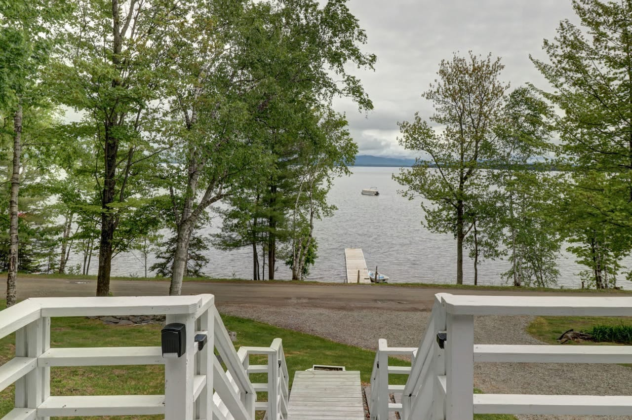 the steps leading down from a cabin towards the dock on moosehead lake